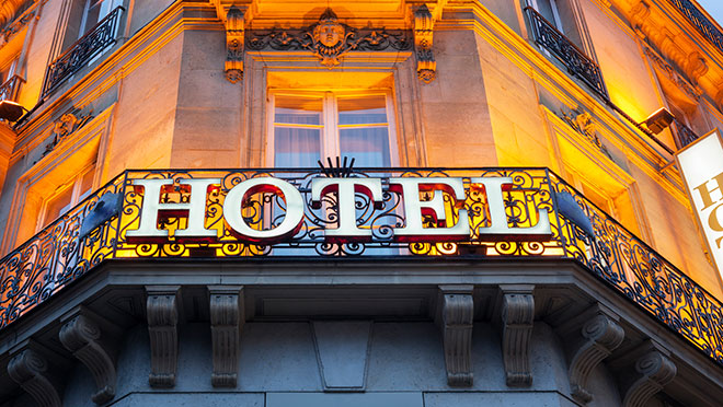 Image of illluminated hotel sign on an old building