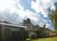 Neighbourhood homes with cloudy sky and lens flare