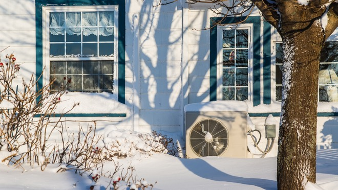 Snowy home exterior heat pump