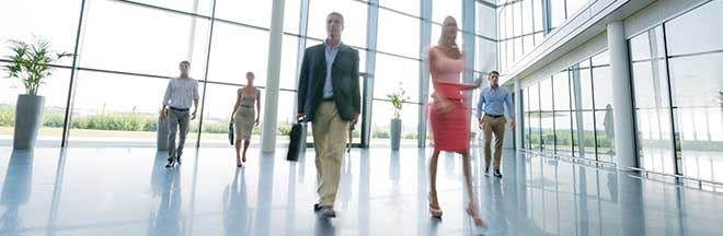 Business people walk through an office building foyer