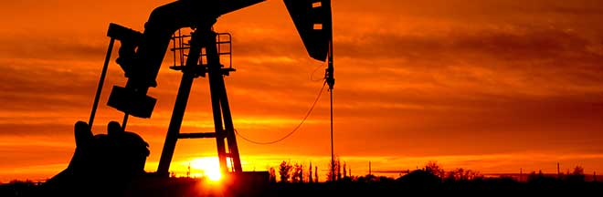 Pump jack in an oil field at sunset
