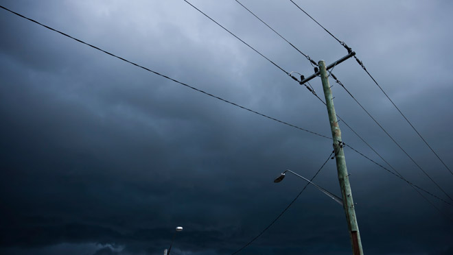 Image of power lines under black storm clouds