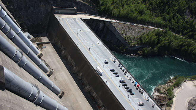 View from top of Revelstoke Dam shows penstocks and parking lot for the Dam Visitor Centre.
