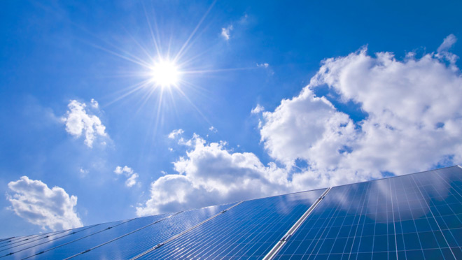 Image of solar panels under a sunny, blue sky