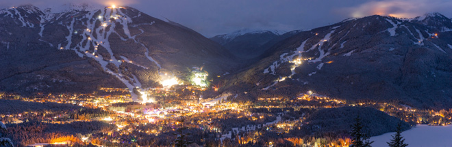 View from nearby mountain of Whistler village, Blackcomb and Whistler mountain ski areas at night.