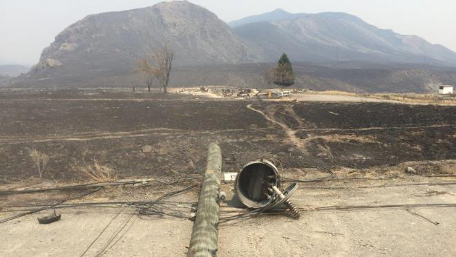 Photo from July 2017 wildfire shows a burned power pole and a charred landscape with smoky haze in the background