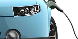 Close up image of an electric car plugged in