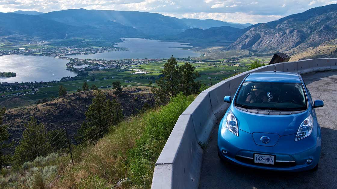 A Nissan Leaf electric vehicle sits parked at a viewpoint on the highway above Osoyoos, B.C.