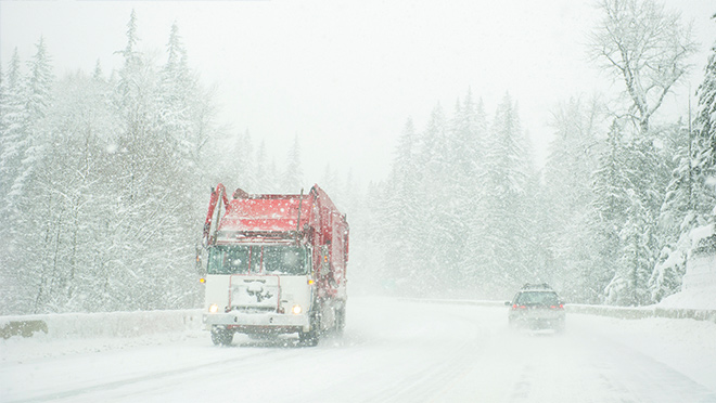 Truck driving down a snowy highway